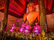 """03 APRIL 2015 - CHIANG MAI, CHIANG MAI, THAILAND: Statues of the Buddha in the """"wiharn"""" (prayer hall) at Wat Phakhao, a temple in Chiang Mai, Thailand. The temple was built between 1487 and 1491 and was the home temple for  Thaomekuthisuthiwong, the 15th King of the Mangrai Dynasty, which ruled Chiang Mai before it became a part of Siam (Thailand).      PHOTO BY JACK KURTZ"""