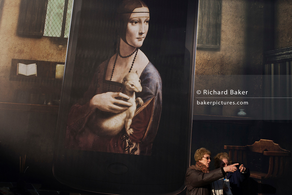 Billboard advertising Leonardo da Vinci's Portrait of Cecilia Gallerani (Lady with an Ermine) above  London tourists at National Gallery.