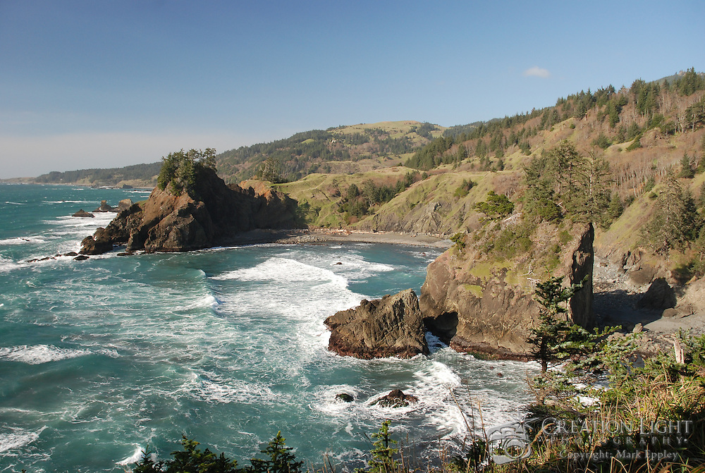 The Oregon coast is marked with rocks that rise above the ocean's surface, some small and some massive.  Here a large rock formation with vertical faces stands high above the Pacific Ocean in a large cove.