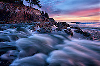Sunrise highlights a rain swollen creek as it merges into the ocean following a storm in Kodiak, Alaska.