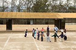 South America, Ecuador, Morocho, village near Cotacachi, children playing circle game outside classroom at elementary school
