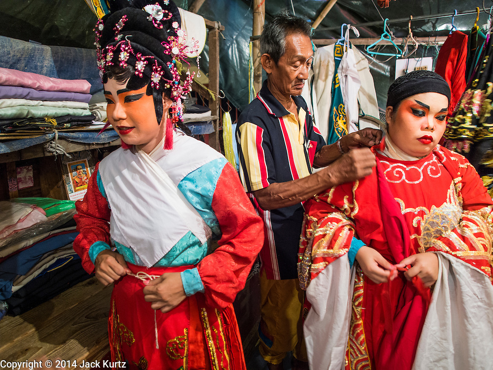 """18 AUGUST 2014 - BANGKOK, THAILAND:       Members of the Lehigh Leng Kaitoung Opera troupe get ready to go on stage before a performance at Chaomae Thapthim Shrine, a small Chinese shrine in a working class neighborhood of Bangkok. The performance was for Ghost Month. Chinese opera was once very popular in Thailand, where it is called """"Ngiew."""" It is usually performed in the Teochew language. Millions of Chinese emigrated to Thailand (then Siam) in the 18th and 19th centuries and brought their culture with them. Recently the popularity of ngiew has faded as people turn to performances of opera on DVD or movies. There are still as many 30 Chinese opera troupes left in Bangkok and its environs. They are especially busy during Chinese New Year and Chinese holiday when they travel from Chinese temple to Chinese temple performing on stages they put up in streets near the temple, sometimes sleeping on hammocks they sling under their stage. Most of the Chinese operas from Bangkok travel to Malaysia for Ghost Month, leaving just a few to perform in Bangkok.   PHOTO BY JACK KURTZ"""