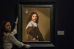 """© Licensed to London News Pictures. 04/12/2015. London, UK. A technician presents """"Portrait of Cornelis Montigny de Glarges, aged 43, half-length, in a brown coat and white lace ruff"""" by Johannes Cornelisz Verspronck (est. £0.1-0.2 million) ahead of Sotheby's London evening sale of Old Master and British paintings on 9th December 2015.  Photo credit : Stephen Chung/LNP"""