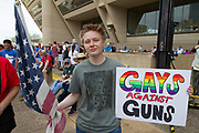 Charlie Black, 15, of Irving, Texas holds an American flag and a protest sign in front of Dallas City Hall. Black was moved to attend the March for Our Lives after seeing the the Pulse nightclub massacre in Florida in TV.