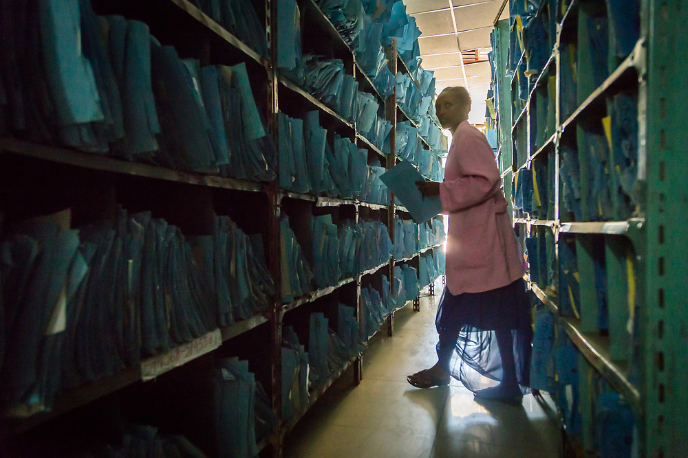 INDIVIDUAL(S) PHOTOGRAPHED: N/A. LOCATION: Felege Hiwot Referral Hospital, Bahir Dar, Ethiopia. CAPTION: The hospital works with paper files, resulting in a large records department. Here, a staff member wanders through the rows, looking for a particular file.