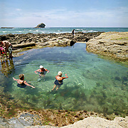 Three elderly women swimming in Portreath Pool, Cornwall, UK. Created by adding a retaining wall to a rock pool, until the 1970s this tidal pool was used by a local school for swimming lessons. Until the 1950s and the rise of the heated indoor swimming pool, children learnt to swim outdoors. For those close to the sea, many man-made tidal swimming pools were constructed around Britain's coastline. Heated by the sun, these tidal pools were often built to keep bathers safe from high and rough seas, which explains why so many of them are clustered in Scotland and around the surfing beaches of Cornwall. Whether they are simple swimming holes made by shoring up natural rock pools or grand lido-like pools complete with lifeguards and tea huts, they are all refreshed by good high tides.