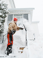 Andrew Bolduc kindly shovels out a friend's walkway on Winter Street before he heads off to work during the height of Wednesday's Nor'Easter that blew through the region.  (Karen Bobotas/for the Laconia Daily Sun)