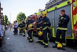 © Licensed to London News Pictures. 19/06/2017. London, UK. Emotional Firefighters who attended the scene of the fire, arrive to observe minutes silence held near the scene of the Grenfell tower block fire. The blaze engulfed the 27-storey building killing dozens - with 34 people still in hospital, many of whom are in critical condition. Photo credit: Ben Cawthra/LNP