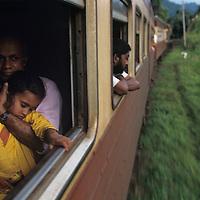 Sri Lanka, Father cradles daughter on railroad through jungle toward Kandy