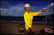 Hawker selling grilled squid walks along a beach in Nha Trang, Khanh Hoa Province, Vietnam, Southeast Asia