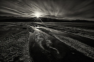 Sunset sunburst reflections at Salt Flats Death Valley.