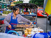 19 OCTOBER 2012 - BANGKOK, THAILAND:  A snack vendor in the Bangkok Flower Market. The Bangkok Flower Market (Pak Klong Talad) is the biggest wholesale and retail fresh flower market in Bangkok.  The market is busiest between 3:30AM and 6AM. Thais grow and use a lot of flowers. Some, like marigolds and lotus, are used for religious purposes. Others are purely ornamental.      PHOTO BY JACK KURTZ