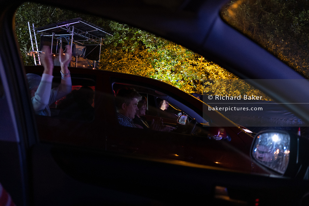 From inside their cars, opera fans applaud the performance of Puccini's La bohème, performed by members of  English National Opera (ENO) as a drive-in (ENO Drive and Live) at Alexandra Palace, on 18th September 2020, in London, England. This is ENO's first public performance since the closure of their West End Colisseum home venue, because of the Coronavirus pandemic lockdown in March. This is Europe's first live drive-in opera production that audiences can safely experience from their cars and ENO's first public performance since the closure of their West End Colisseum home venue, because of the Coronavirus pandemic lockdown in March. As per the latest government advice. Each bubbled group consists of; 34 members of the<br /> ENO Orchestra, 20 ENO Chorus members and 8 principals. Each bubble has its own individual crew to oversee their rehearsals and performances.
