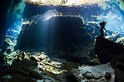 Mexico, Quintana Roo. A freediver champion is sitting on a rock extending her arm, reaching for the beautiful sun rays at Cenote Chac Mol.