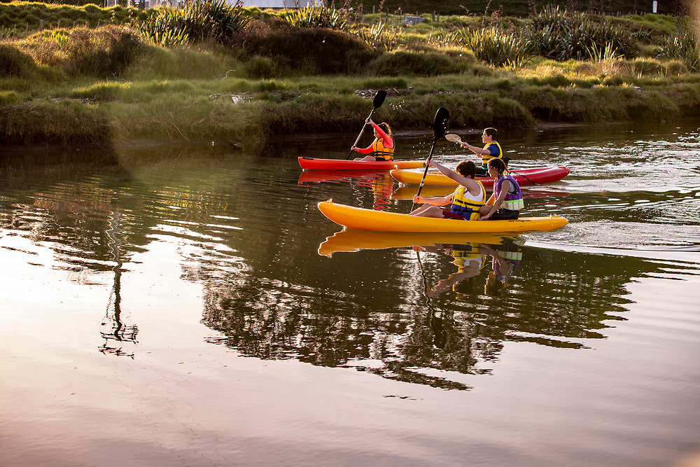 Young people kayaking on estuary waters at<br /> Whangapoua Beach,East Coast, North Island