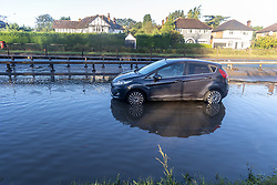 Licensed to London News Pictures. 05/10/2021. London, UK. An abandon car stuck in flood water on the A3 Kingston Bypass, South West London this morning. The A3 a main route in and out of London was closed this morning after torrential rain caused flooding on the carriage way as traffic built up on surrounding roads. Torrential rain last night has caused severe wide spread flooding in London with many roads blocked with flood water and broken down cars. Photo credit: Alex Lentati/LNP