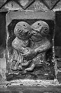 The Stone Bestiary - Black and white photo art print of Norman Romanesque exterior corbel no 45  - sculpture of what is probably a morality tale. A man and women are grasping each other. The women seems to be clutching the mans buttocks and he has clasped her hand as if resisting. He also seems to be resisting an embrace. The Norman Romanesque Church of St Mary and St David, Kilpeck Herefordshire, England. Built around 1140 .<br /> <br /> Visit our LANDSCAPE PHOTO ART PRINT COLLECTIONS for more wall art photos to browse https://funkystock.photoshelter.com/gallery-collection/Places-Landscape-Photo-art-Prints-by-Photographer-Paul-Williams/C00001WetsxVxNTo