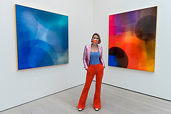 © Licensed to London News Pictures. 21/10/2020. LONDON, UK. British artist Nat Bowen poses with two of her resin works. Bowen uses the study of Chromology, the psychology behind colour, as a way to communicate non verbally through her work. Preview of STARTnet Art Fair at the Saatchi Gallery in Chelsea.  The contemporary art fair showcases local London, as well as international, galleries and individual artists from all over the world.  The fair runs 21 to 25 October with Covid-19 protocols in place for visitors.   Photo credit: Stephen Chung/LNP