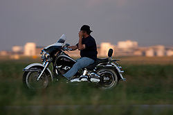 A man in a reversed baseball cap adjusts his sunglasses as he rides his Harley on a road in Minnesota