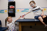 Alaina Bodily, 2, hands her brother, Joseph, 5, a crayon while during an appointment with Dr. Laura Workman, a geneticist at Sutter Memorial Hospital in Sacramento, California. The siblings have Stickler syndrome. January 6, 2010.