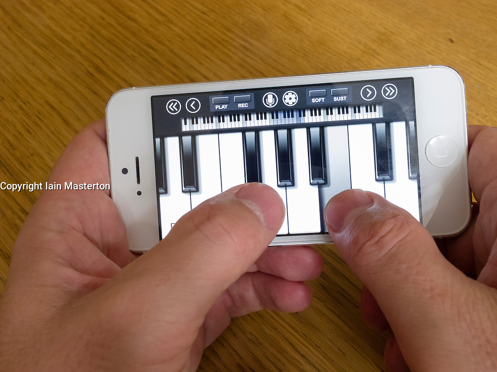 using white iPhone 5 smartphone to play piano on touch keyboard using music app
