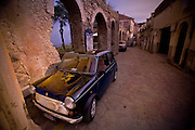A small blue car is parked on a brick road inside old walls in ruins.