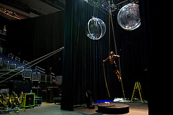 """Ryan Schneider, who rides a motorcycle on a highwire during the show, practices a new act after a performance in Washington D.C. It is common for the performers to exercise and practice their routines after shows, taking advantage of the adrenaline from the evening's event.<br /> <br /> Ringling Bros. and Barnum & Bailey Circus started in 1919 when the circus created by James Anthony Bailey and P. T. Barnum merged with the Ringling Brothers Circus. Currently, the circus maintains two circus train-based shows, the Blue Tour and the Red Tour, as well as the truck-based Gold Tour. Each train is a mile long with roughly 60 cars: 40 passenger cars and 20 freight. Each train presents a different """"edition"""" of the show, using a numbering scheme that dates back to circus origins in 1871 — the first year of P.T. Barnum's show."""