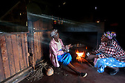 The mother and sister-in-law of Kibet Serem chat while a pot of milk heats over a fire to make yogurt in their village near Kericho, Kenya. (From the book What I Eat: Around the World in 80 Diets.) Kibet looks after a tea plantation that his father planted on their property when Kibet was a young boy and is responsible for milking the cows that his family owns. He sells extra milk to a nearby school for a government feeding program and gives some to his mother who makes yogurt and sells it. Their staple food is ugali, a maize meal porridge.