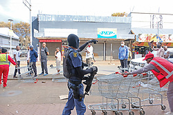 JOHANNESBURG, SOUTH AFRICA - APRIL 18: A SAPS officer ensures social distancing, during a South African Police Service (SAPS) Metro Police and Army supported patrol in Rockey Street, Yeoville. Random searchs and social distancing measures on April 18, 2020 in Johannesburg South Africa. Under pressure from a global pandemic. President Ramaphosa declared a 21 day national lockdown extended by another two weeks, mobilising goverment structures accross the nation to combat the rapidly spreading COVID-19 virus - the lockdown requires businesses to close and the public to stay at home during this period, unless part of approved essential services. (Photo by Dino Lloyd)