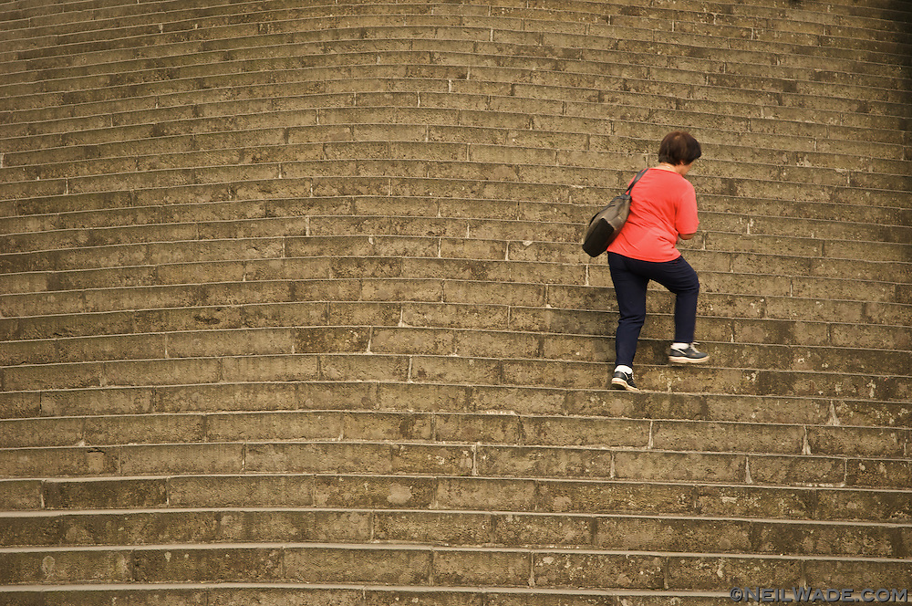 A woman climbs the curved stone stairs to the Zhi Nan Temple in Taipei, Taiwan.