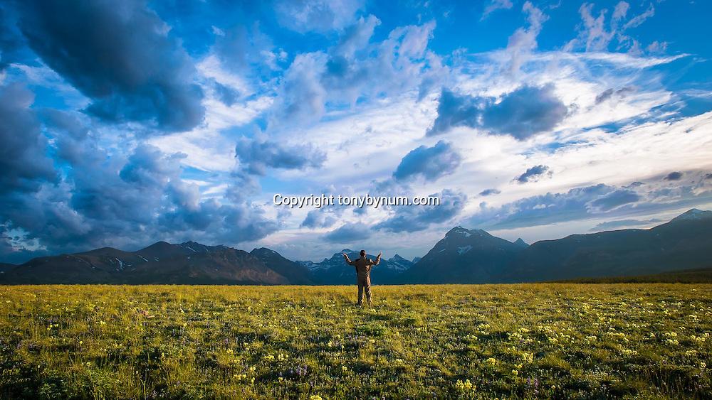 man raising arms toward clearing storm clouds