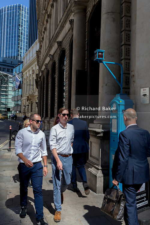 Businessmen walk past one of the few remaining police signal boxes on Threadneedle Street in the City of London, the capital's historic financial district, on 2nd August 2018, in London, England. The Police box is a public telephone kiosk or callbox for the use of members of the police, or for members of the public to contact the police. It was introduced in the United States in 1877 and was used in the United Kingdom throughout the 20th century from the early 1920s.