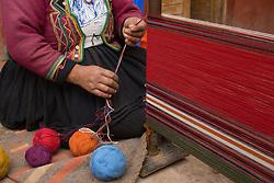 South America, Peru, Chinchero (near Cuzco), woman weaving using traditional loom.  MR