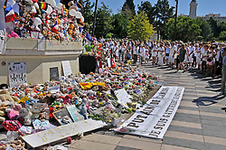 """People dressed in white gather around the make shift memorial as they attend a minute of silence held for the victims of the Bastille Day attack in the city of Nice, southeastern France, on August 07, 2016. Eighty-five people were killed and many were wounded after a jihadist ploughed a 19-tonne truck into a massive crowd celebrating Bastille Day, killing 85 people and wounding more than 400 others along the famous Promenade des Anglais during the July 14 celebrations. 85 balloons and 85 stars were stick in homage to 85 victims. A banner reading 'ce Putain de camion' (""""Damn Truck"""" - title is a French song, singer Renaud dedicated the song to his friend and fellow actor Coluche who died on 19 June 1986 in a motorbike accident with a truck between) Photo by Pierre Rousseau/Cit'images/ABACAPRESS.COM"""