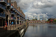 View looking across Shadwell Basin in Wapping towards Canary Wharf financial district. on 24th May 2021 in London, United Kingdom. In the distance there is a very old tilt bridge designed by Marc Brunel.
