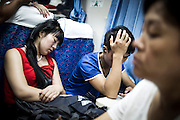 "A Chinese woman takes a rest on a train seat in PingYao, China, July 28, 2014. <br /> <br /> This image is part of the series ""24/7"", an ironic view on restless and fast-growing Chinese economy described through street vendors and workers sleeping during their commercial daily activity.<br /> <br /> © Giorgio Perottino"
