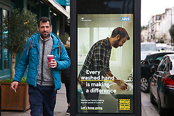 © Licensed to London News Pictures. 26/03/2021. London, UK. A man walks past the government's 'Every washed hand is making a difference' poster in north London as MPs voted to extended emergency Covid-19 powers for another 6 months. The next key date for restrictions easing is Monday 29 March 2021, when the 'Stay at Home' guidance will be dropped. Photo credit: Dinendra Haria/LNP