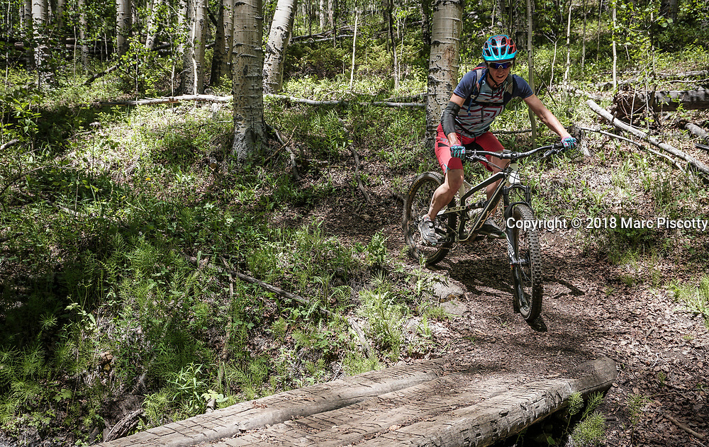 SHOT 6/10/18 11:54:42 AM - Vesta Lingvyte of Denver, Co. crosses a small bridge while mountain biking the Colorado Trail near Granite, Colorado. The Colorado Trail is a long-distance trail running for 486 miles (782 km) from the mouth of Waterton Canyon southwest of Denver to Durango in Colorado, United States. Its highest point is 13,271 feet (4,045 m) above sea level, and most of the trail is above 10,000 feet (3,000 m). Despite its high elevation, the trail often dips below the alpine timberline to provide refuge from the exposed, storm-prone regions above. (Photo by Marc Piscotty / © 2018)