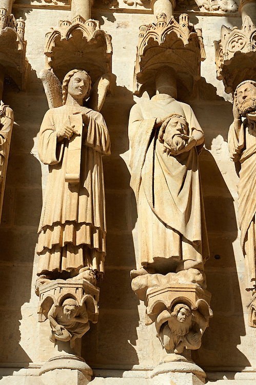 Gothic statues of an  array of saints.  Gothic Cathedral of Notre-Dame, Amiens, France . The Cathedral Basilica of Our Lady of Amiens or simply Amiens Cathedral, is a Roman Catholic  cathedral the seat of the Bishop of Amiens. It is situated on a slight ridge overlooking the River Somme in Amiens. Amiens Cathedral, was built almost entirely between 1220 and c.1270, a remarkably short period of time for a Gothic cathedral, giving it an unusual unity of style. Amiens is a classic example of the High Gothic style of Gothic architecture. It also has some features of the later Rayonnant style in the enlarged high windows of the choir, added in the mid-1250s. Amiens Cathedra has been listed as a UNESCO World Heritage Site since 1981. Photos can be downloaded as Royalty Free photos or bought as photo art prints. <br /> <br /> Visit our MEDIEVAL PHOTO COLLECTIONS for more   photos  to download or buy as prints https://funkystock.photoshelter.com/gallery-collection/Medieval-Middle-Ages-Historic-Places-Arcaeological-Sites-Pictures-Images-of/C0000B5ZA54_WD0s