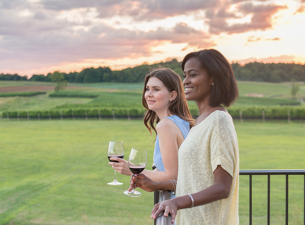 Young women drink wine together on a balcony at a winery.