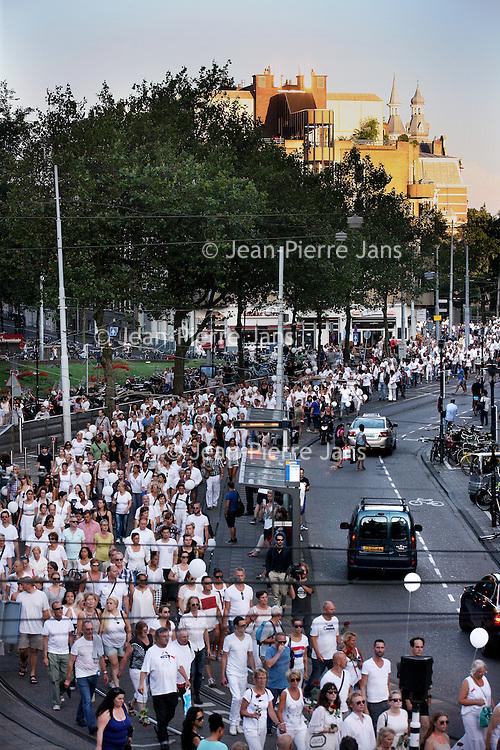 Nederland, Amsterdam , 23 juli 2014.<br /> Duizenden mensen lopen mee met een stille tocht door het centrum van Amsterdam. Volgens de organisatie zijn er zo'n vijfduizend deelnemers, meldt persbureau Novum. De wandeling begon om 20.00 uur op de Dam en eindigt daar ook weer. Deelnemers zullen daar witte ballonnen oplaten. Ook dragen zij witte kleding.<br /> Foto: Stille tocht passeert het Leidseplein.<br /> Thousands of people in white clothes walk along with a silent march through the center of Amsterdam. The victims of flight MH17 are thus commemorated. National day of Mourning .