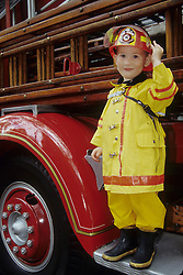 United States, Washington, Seattle, boy in fireman costume on fire truck during annual Pioneer Square Fire Festival