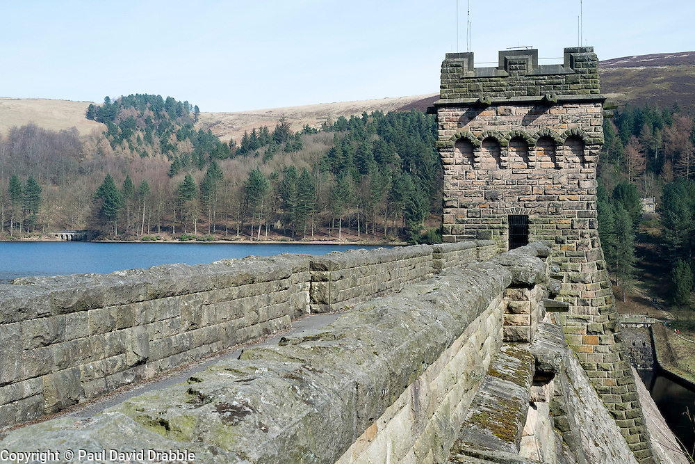 """Derwent Reservoir in Derbyshire, England is the middle of three reservoirs in the Upper Derwent Valley, the higher reservoir being Howden to the North and the lower being Ladybower to the south. Between them they provide practically all of Derbyshire's water, as well as to a large part of South Yorkshire and as far afield as Nottingham and Leicester.<br /> Begun in 1902 this neo-Gothic solid masonry dam wall is built from huge stones that were transported along a specially created railway from the quarries at Grindleford. Over 1,000 workers lived in a specially constructed and self-contained town of Birchinlee also known as """"Tin Town"""". Derwent reservoir began being filled in November 1914, and overflowed for the first time in January of 1916. Covering an area of 70.8 hectares (175 acres) and at its deepest point is 34.7 metres (114 ft) the dam can support a total of 9.64 million cubic metres of water.<br /> For 6 weeks during the Second World War the reservoir was used by the pilots of the 617 Squadron """"the Dambusters"""" to practice their low-level flying skills needed for Operation Chastise, because of the Derwents similarity to the operations German target. In for 2 weeks in 1954 the the sound of Lancaster bomber engines could be heard again over the Derwent as the reservoir stood in for the German dams a second time. This time for the filming of the """"The Dambusters"""" starring Richard Todd as Guy Gibson. The west tower of the dam wall is home to Derwent Valley Museum and includes a permanent memorial to 617 Squadron to which is visible even when the Museum is closed. <br /> <br /> 22  March 2015 Image © Paul David Drabble www.pauldaviddrabble.co.uk"""