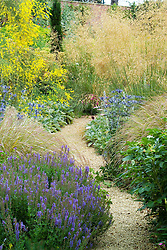 Path through borders of grasses and perennials at Broughton Grange