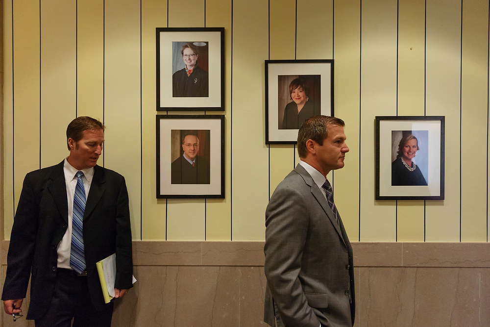 Members of the House Judiciary Committee walk by portraits of the remaining court Justices while touring the offices of the West Virginia Supreme Court of Appeals in Charleston, W.V. on Monday, August 6th, 2018. Justice Menis Ketchum retired from his seat one day before West Virginia lawmakers were to consider whether the state Supreme Court justices deserved to be impeached for corruption.
