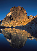 "Sunrise light strikes Snowpatch Spire (10,050 feet) and reflects in a mountain pond (tarn) in Bugaboo Provincial Park, British Columbia, Canada. The Bugaboos are a range in the Purcell Mountains, which are a subrange of the Columbia Mountains, which are west of the Rocky Mountain Trench. (Some USA maps label the ""Percell Mountains"" where their southern limit protrudes into the states of Idaho and Montana.) The igneous Bugaboo intrusion of 135 million years ago cooled into hard crystalline granite and was scraped into spires by glaciers eroding surrounding rock dating from 600 million to 1 billion years ago. Published in ""Light Travel: Photography on the Go"" book by Tom Dempsey 2009, 2010."