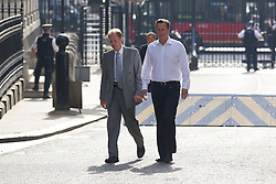 © Licensed to London News Pictures. 16/07/2013. London, UK. The British Prime Minister, David Cameron (R), looks relaxed as he walks in Downing Street after dropping off his youngest daughter, Florence, at daycare in London today (16/07/2013). Photo credit: Matt Cetti-Roberts/LNP