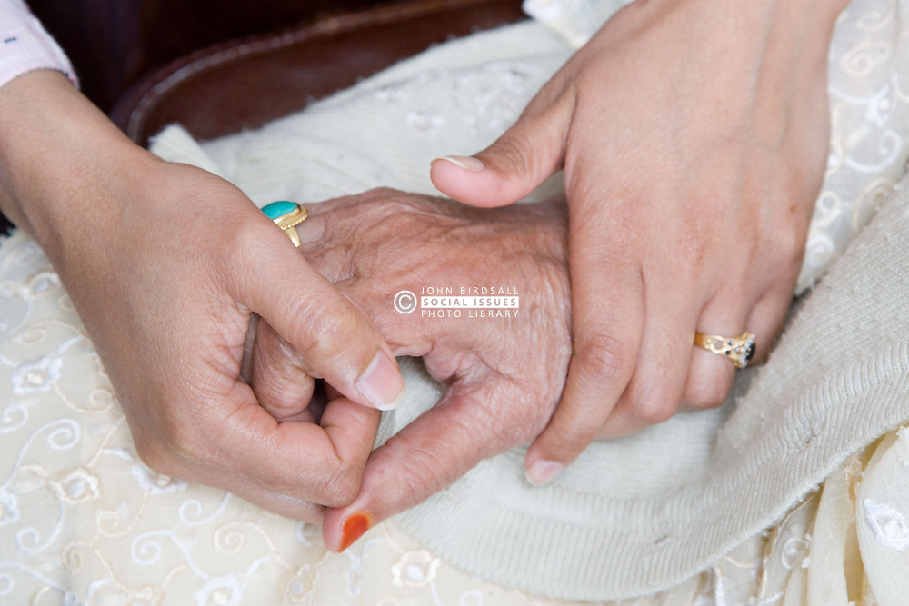 Young female carer holding an older woman's hands,