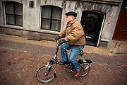 Een man fietst op een vouwfiets door Utrecht
