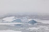 Fog shrouds the coastline as the KK approaches Peter 1 Øy, Bellingshausen Sea, Phantom Coast, Western Antarctica